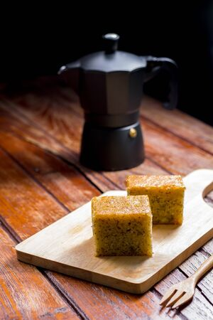 Close up square cut of homemade sweet and solf banana cake on wooden chopping board and fork on table with solf focus black moka pot. Delicious and healthy bakery.