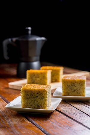 Close up square cut of homemade sweet and solf banana cake on white plate on table with solf focus black moka pot. Delicious and healthy bakery.