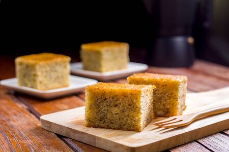 Close up square cut of homemade sweet and solf banana cake on wooden chopping board and fork on table. Delicious and healthy bakery.