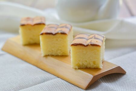 Cube cut of butter cake on wooden tray and table for served in party. Delicious dessert eat with tea and coffee in morning.