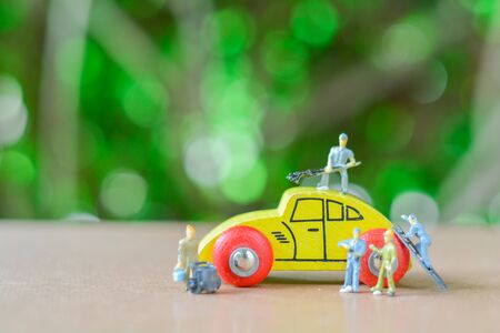 Group of teamwork Miniature people, small model human figure cleaning wooden yellow car with green bokeh background. Copy space for your text. Business and financial concept.