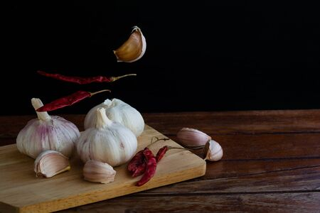 Group of garlic on chopping board and some garlic cloves floating in the air and red dried chilli on wooden table with black background. Copy space for your text.