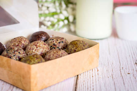Healthy snack. Energy ball with date plam, black and white sesame, chia and rasin in ceramic bowl on wooden table. Vegan vegetarian.