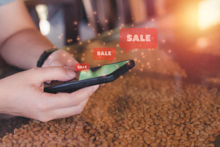 Shopping online concept. Hand holding black smartphone with red popup sale. Black Friday and shop at home.