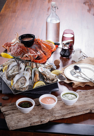 Seafood Plate of crustacean seafood with fresh lobster, mussels, oysters on dining table