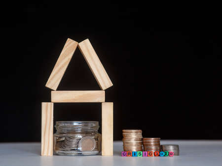 Glass bank with many world coins, house word or label on money jar and wooden home geometric blocks over table Reklamní fotografie