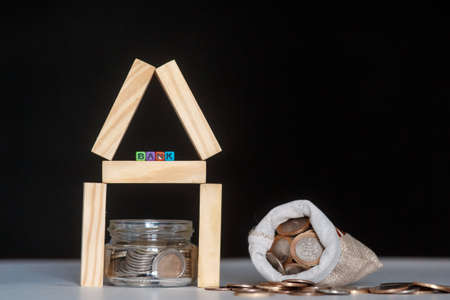 Glass bank with many world coins, house word or label on money jar and wooden home geometric blocks over table Stok Fotoğraf