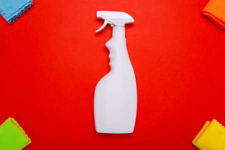 glass cleaner spray. cleaning agent white spray for cleaning glass with rags on a red background