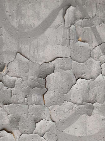 Old gray wall with cracks in plaster and paint. Destruction Фото со стока