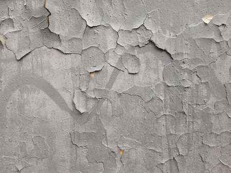 Old gray wall with cracks in plaster and paint. Destruction graffiti