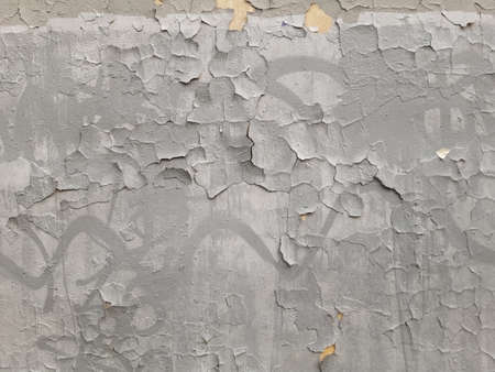 Old gray wall with cracks in plaster and paint. Destruction of graffiti Фото со стока