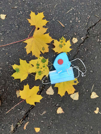 Coronavirus autumn. Yellow maple leaf, respirator and disposable medical mask on wet asphalt. Virus. Influenza