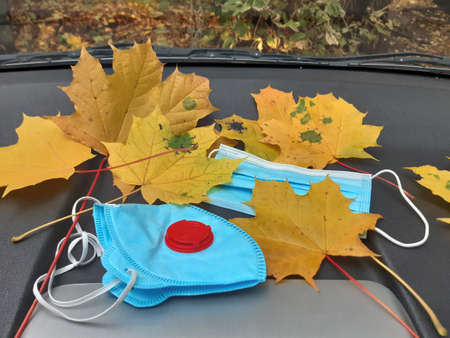 Coronavirus autumn. Yellow maple leaf, respirator and medical disposable mask lying on the front panel of the car