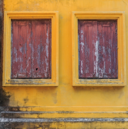 Old windows on yellow wall photo