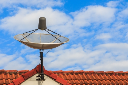 Satellite dish on red roof photo