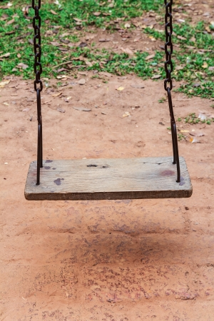 Old wooden swing on the playground in the park photo