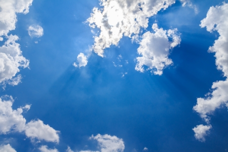 Sun ray shining through the clouds in the blue sky photo