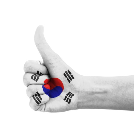 Hand with thumb up, South Korea flag painted as symbol of excellence, achievement, good - isolated on white background photo