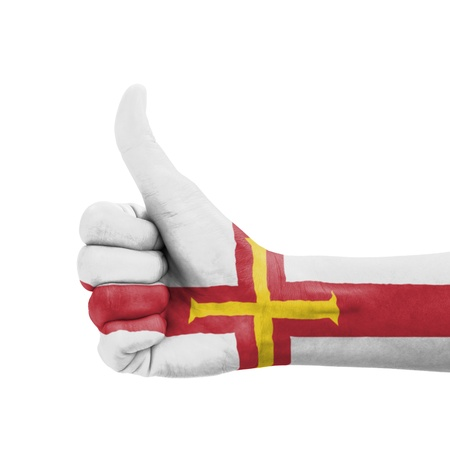 Hand with thumb up, Guernsey flag painted as symbol of excellence, achievement, good - isolated on white background photo