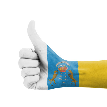 Hand with thumb up, Canary Islands flag painted as symbol of excellence, achievement, good - isolated on white background photo