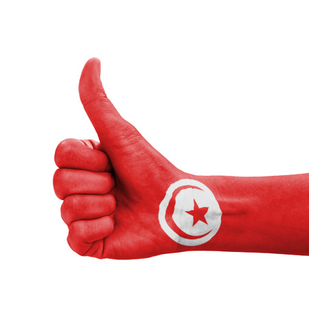 Hand with thumb up, Tunisia flag painted as symbol of excellence, achievement, good - isolated on white background photo