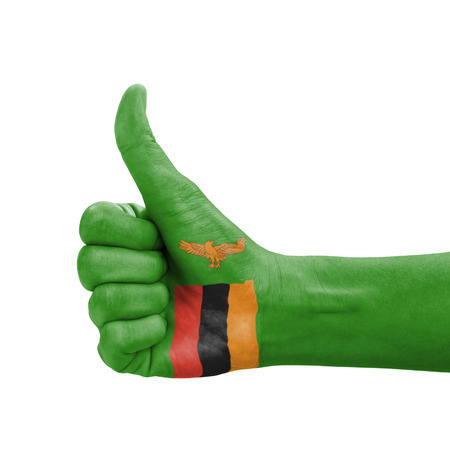 Hand with thumb up, Zambia flag painted as symbol of excellence, achievement, good - isolated on white background