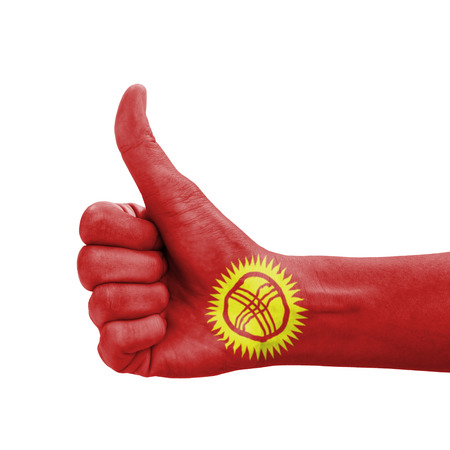 Hand with thumb up, Kyrgyzstan flag painted as symbol of excellence, achievement, good - isolated on white background photo