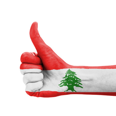 Hand with thumb up, Lebanon flag painted as symbol of excellence, achievement, good - isolated on white background photo