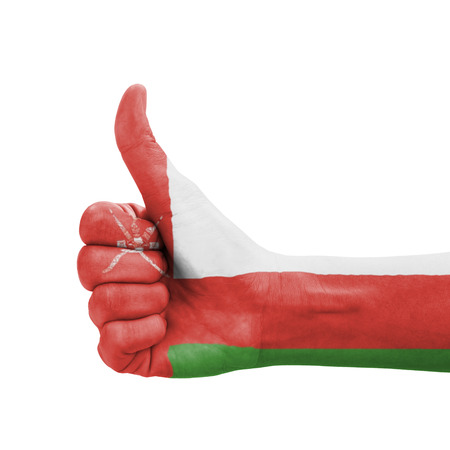 Hand with thumb up, Oman flag painted as symbol of excellence, achievement, good - isolated on white background photo