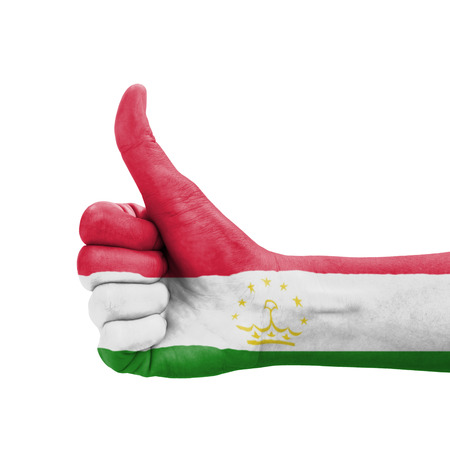 Hand with thumb up, Tajikistan flag painted as symbol of excellence, achievement, good - isolated on white background photo