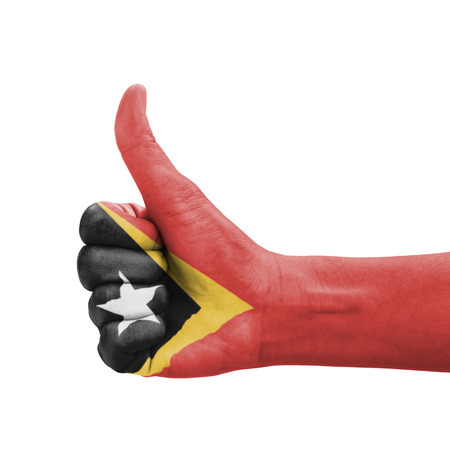 Hand with thumb up, Timor-Leste flag painted as symbol of excellence, achievement, good - isolated on white background photo