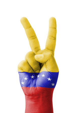 Hand making the V sign, Venezuela flag painted as symbol of victory, win, success - isolated on white background photo