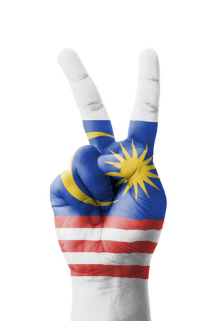 winning flag: Hand making the V sign, Malaysia flag painted as symbol of victory, win, success - isolated on white background Stock Photo