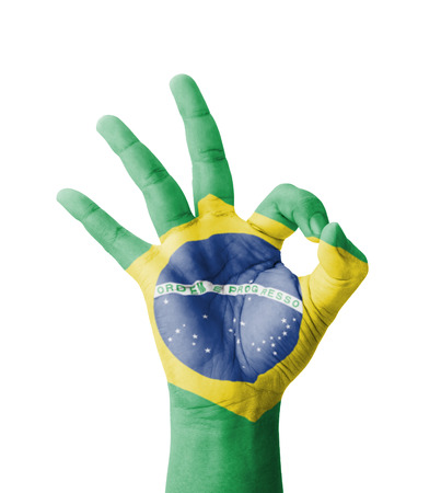 Hand making Ok sign, Brazil flag painted as symbol of best quality, positivity and success - isolated on white background photo
