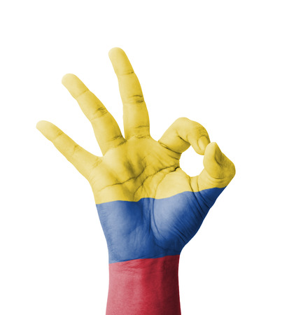 Hand making Ok sign, Colombia flag painted as symbol of best quality, positivity and success - isolated on white background Фото со стока