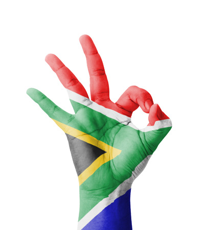 Hand making Ok sign, South Africa flag painted as symbol of best quality, positivity and success - isolated on white background photo