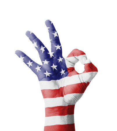 Hand making Ok sign, USA (United States of America) flag painted as symbol of best quality, positivity and success - isolated on white background Фото со стока