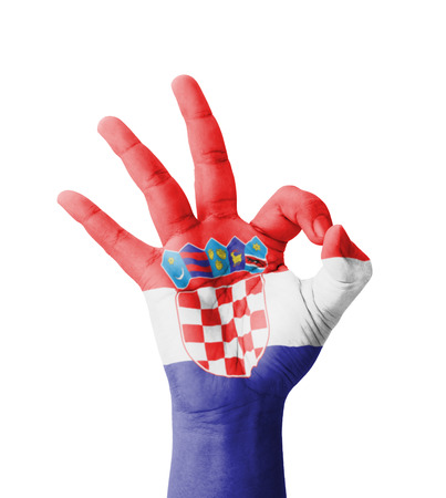 Hand making Ok sign, Croatia flag painted as symbol of best quality, positivity and success - isolated on white background photo