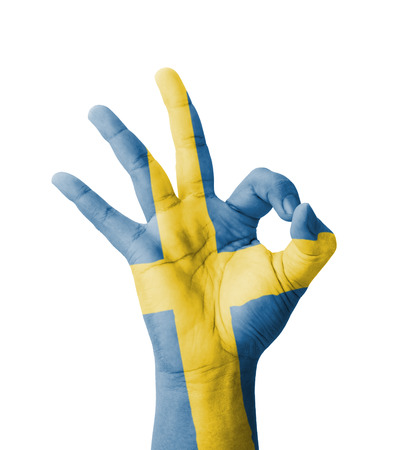 Hand making Ok sign, Sweden flag painted as symbol of best quality, positivity and success - isolated on white background photo