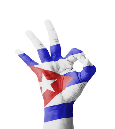 Hand making Ok sign, Cuba flag painted as symbol of best quality, positivity and success - isolated on white background photo