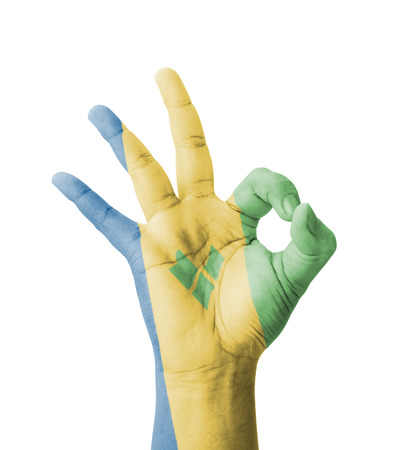 Hand making Ok sign, Saint Vincent and the Grenadines flag painted as symbol of best quality, positivity and success - isolated on white background photo