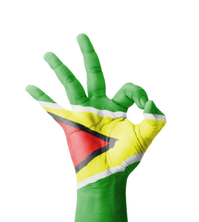Hand making Ok sign, Guyana flag painted as symbol of best quality, positivity and success - isolated on white background photo