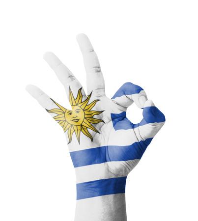 bandera de uruguay: Mano haciendo signo ok, Uruguay bandera pintada como s�mbolo de la mejor calidad, la positividad y el �xito - aislados en fondo blanco Foto de archivo