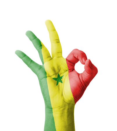 Hand making Ok sign, Senegal flag painted as symbol of best quality, positivity and success - isolated on white background