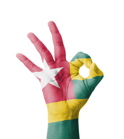 Hand making Ok sign, Togo flag painted as symbol of best quality, positivity and success - isolated on white background photo