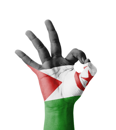 Hand making Ok sign, Western Sahara flag painted as symbol of best quality, positivity and success - isolated on white background photo