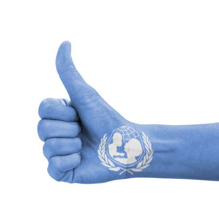 nazioni unite: Mano con il pollice in su, UNICEF (Fondo delle Nazioni Unite) bandiera dipinta come simbolo di eccellenza, realizzazione, buona