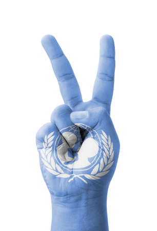 Hand making the V sign, UNICEF (United Nations Childrens Fund) flag painted as symbol of victory, win, success photo