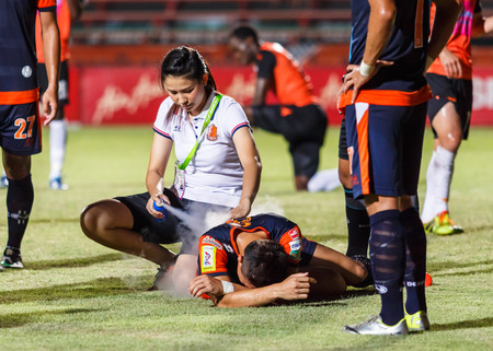 SISAKET THAILAND-MAY 24: First aid team of Udonthani FC. (white) in action during Regional League between Sisaket Utd. and Udonthani FC. at Sri Nakhon Lamduan Stadium on May 24,2014,Thailand