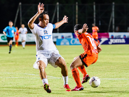 possession: SISAKET THAILAND-JULY 13: Patiparn Phetphun of TOT S.C. (white) in action during Thai Premier League between Sisaket FC and TOT SC at Sri Nakhon Lamduan Stadium on July 13,2014,Thailand Editorial